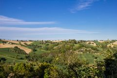 Hilly landscape of the Tuscan countryside near Siena. The sky is almost serene of intense blue and the cultivated hills can be glimpsed Stock Images