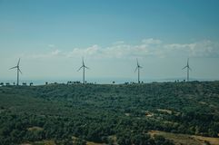 Hilly landscape with wind turbines for electric power generation. Hilly landscape covered by trees and several wind turbines for electric power generation, on royalty free stock images