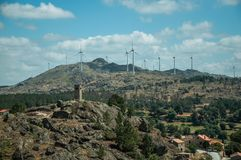 Hilly landscape with wind turbines on top. Hilly landscape covered by trees and rocks with wind turbines and gothic tower on top, in a sunny day at Sortelha. One royalty free stock photo