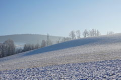 Hilly landscape in winter with a tall electricity pylon leading high electric current in the background Royalty Free Stock Photos