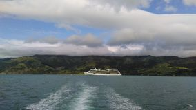 Hilly mountains. Cruise ship in Akaroa Royalty Free Stock Photos