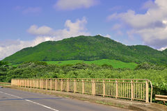 Hilly Road with Barrier and mountainous background around Mahebourg, Mauritius. Hilly narrow Road in blue cloudy sky with metal steel Barrier and green Stock Photo