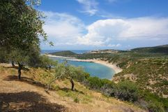 Hilly southern landscape with olive trees and their shadow, sea view, rocky beach, clouds stock photo