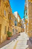 The hilly streets in medieval Birgu, Malta. Walk the hilly street of medieval fortified city of Birgu, lined with historical residential edifices, Malta stock photo
