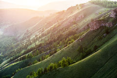 The hilly terrain with green grass at sunset. Summer landscape in mountains with the sun Stock Photo