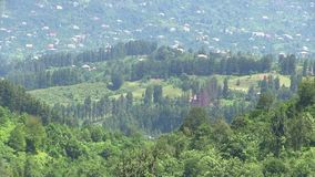 Hilly terrain. Panorama of a hilly terrain with dwelling houses and a spur of a low mountain ridge stock footage