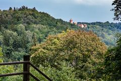 Wooded area with a castle in the distance. A hilly, wooded area with a castle in the distance, in the forefront there are wooden stairs going down royalty free stock photography