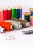 Hilo coloreado con las tijeras en el fondo blanco Fotografía de archivo libre de regalías
