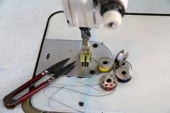 Hilo colorido en las bobinas, el color azul y blanco amarillo rojo, con las tijeras Clippers puestos en la máquina de coser Fotografía de archivo