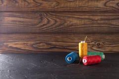 Hilo de coser en bobinas, tela, agujas para coser en fondo de madera Fije para adaptar productos, hacer punto, las aficiones y el Fotos de archivo libres de regalías