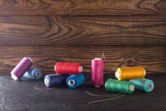 Hilo de coser en bobinas, tela, agujas para coser en fondo de madera Fije para adaptar productos, hacer punto, las aficiones y el Foto de archivo libre de regalías