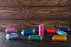 Hilo de coser en bobinas, tela, agujas para coser en fondo de madera Fije para adaptar productos, hacer punto, las aficiones y el Fotos de archivo