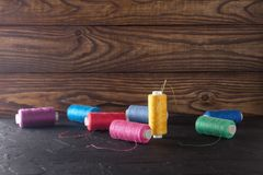 Hilo de coser en bobinas, tela, agujas para coser en fondo de madera Fije para adaptar productos, hacer punto, las aficiones y el Fotografía de archivo