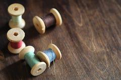Hilo de coser en un fondo de madera Sistema de hilos en las bobinas Imágenes de archivo libres de regalías