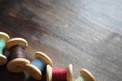 Hilo de coser en un fondo de madera Sistema de hilos en las bobinas Imagenes de archivo