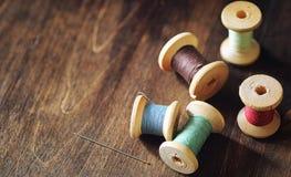 Hilo de coser en un fondo de madera Sistema de hilos en las bobinas Foto de archivo