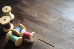 Hilo de coser en un fondo de madera Sistema de hilos en las bobinas Fotos de archivo