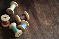 Hilo de coser en un fondo de madera Sistema de hilos en las bobinas Imagen de archivo