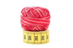 Hilo de coser rojo encima de la cinta métrica amarilla Accesorios y herramientas de costura Imagenes de archivo
