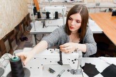 Hilo de la fijación de la costurera en la máquina de coser Fotos de archivo libres de regalías