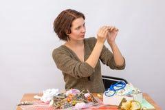 Hilo de la muchacha una aguja en la tabla con costura Imagen de archivo