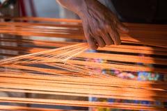 Hilo de seda anaranjado en el telar de costura o, textura, backgrou foto de archivo