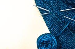 Hilo del algodón con las agujas que hacen punto de acrílico y una bola del azul en un fondo blanco foto de archivo libre de regalías