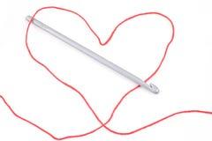 Hilo en forma de corazón, ganchillo y madeja roja Imagen de archivo