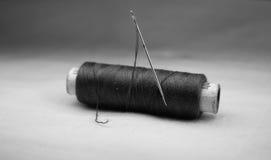 Hilo negro con la aguja Fotografía de archivo