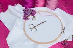 Hilo rosado y tela blanca en el marco de bordado de madera para Foto de archivo
