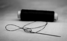 Hilo y aguja negros en el paño blanco Fotos de archivo
