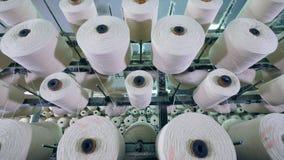 Hilos blancos en las bobinas que hacen girar en una máquina de la fábrica metrajes