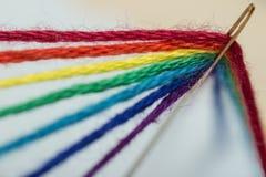 Hilos coloridos en una aguja Fotos de archivo