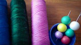 Hilos de coser coloridos con las burbujas coloridas en el fondo de madera Fotos de archivo libres de regalías