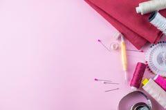 Hilos de coser coloridos en un fondo rosado, endecha plana imagenes de archivo