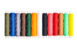 Hilos de coser de diverso color en un rollo Fotos de archivo