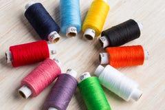 Hilos de las bobinas multicolores Herramientas de costura viejas en el fondo de madera Imagen de archivo libre de regalías