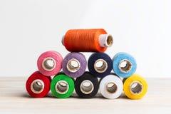 Hilos de las bobinas multicolores Herramientas de costura viejas en el fondo de madera Imagenes de archivo