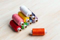 Hilos de las bobinas multicolores Herramientas de costura viejas en el fondo de madera Imágenes de archivo libres de regalías