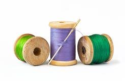 Hilos en los carretes y aguja de costura de madera imagenes de archivo
