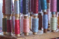 Hilos multicolores de costura de los colores en colores pastel suaves del vintage en spo Foto de archivo