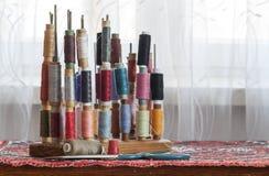 Hilos multicolores de costura de los colores en colores pastel suaves del vintage en spo Fotos de archivo