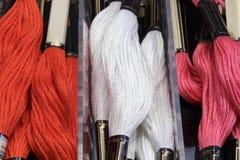 Hilos trenzados del algodón de varios colores (rojos, blanco y rosa) Foto de archivo libre de regalías
