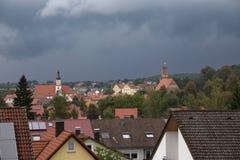 Hilpoltstein with Catholic parish church St. Johann Baptist and castle ruin under stormy sky Royalty Free Stock Image