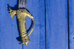 Hilt Of Sword. Hilt of a retro sword laid on the wood painted in blue, overhead view Stock Image