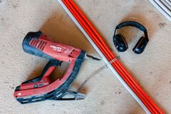 Hilti nail gun next to headphones and a nail-mounted tie royalty free stock photos
