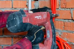 Hilti`s nail gun driving a nail into a wall. With hands stock image