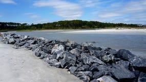 Hilton Head Island, South Carolina beach, rocky barrier. Rock barrier down part of a beach on Hilton Head Island. A sunny day on the beach lines with trees on Stock Photos