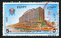 Hilton Hotel. EGYPT - CIRCA 1989: stamp printed by Egypt, shows Nile Hilton Hotel, city, beach, sailboats, circa 1989 stock photo