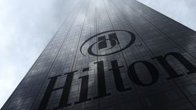 Hilton Hotels Resorts logo on a skyscraper facade reflecting clouds. Editorial 3D rendering. Hilton Hotels Resorts logo on a skyscraper facade reflecting clouds Royalty Free Stock Photography